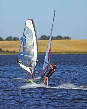 Two windsurfers make the most of the strong winds.