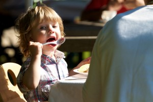 Child licking the jam spoon with relish at a farmhouse brunch