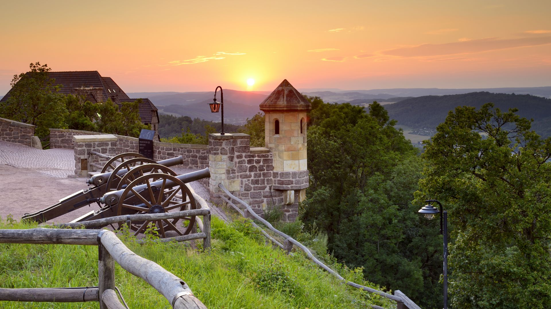 Eisenach: View over two cannons in front of the Wartburg castle to the sunset in the Thuringian Forest