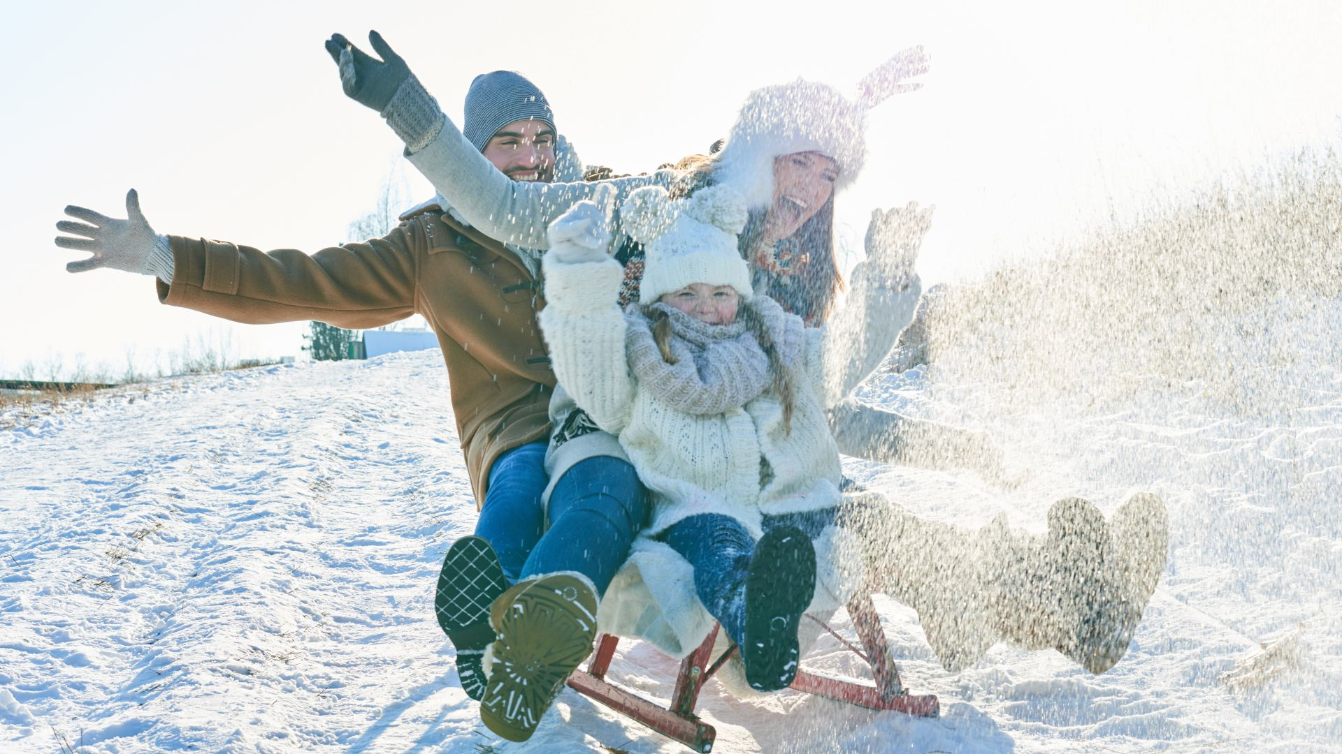 Happy Family Sledding On Snow Covered Field